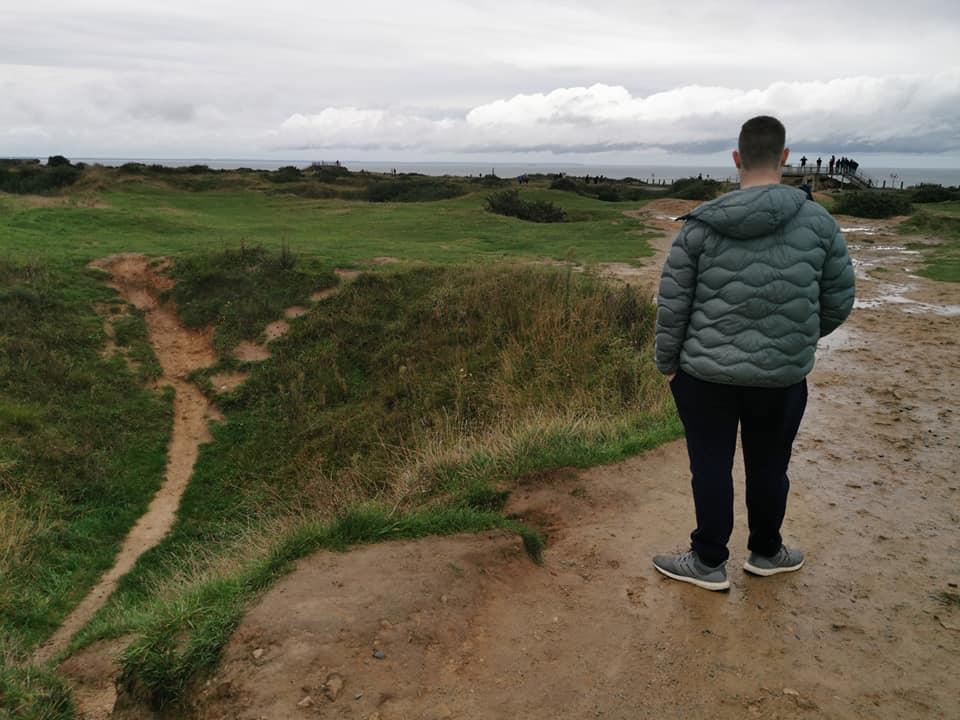 William ved siden af et krater ved Pointe du Hoc